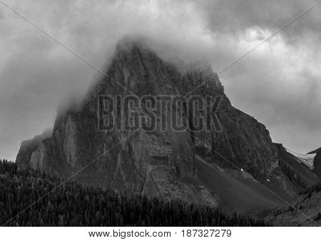A black and white photo of a solitary mountain in Kananaskis country shrouded in clouds.
