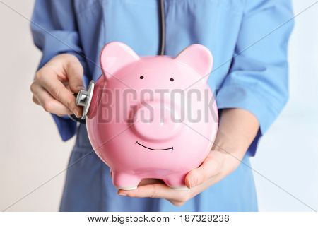 Female doctor holding piggy bank and stethoscope, close up. Concept of medical insurance