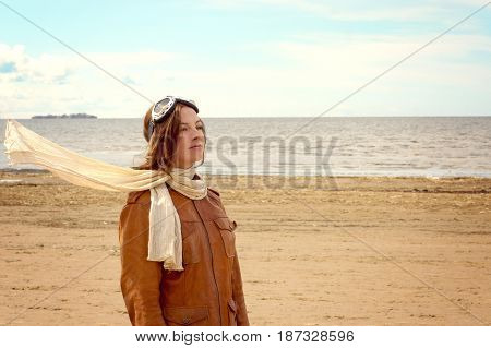Young woman in the pilot's clothes stands on the shore of the bay and looks into the distance, a white scarf flies from the wind.