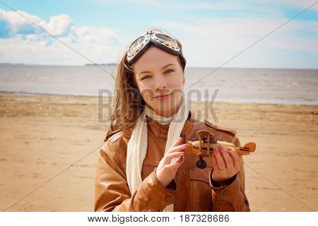 A young woman in a pilot's clothing is standing on the shore of the bay and holds a wooden airplane in her hand.