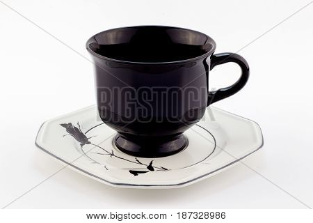 Black retro teacup on white saucer with black rose isolated on white background - English tea