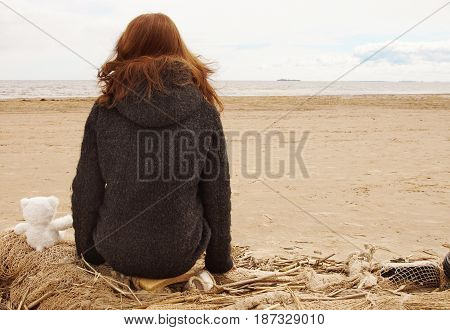 The girl sits on a fishing net and looks at the water of the bay, next to a teddy bear with her back.