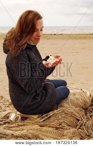Young red-haired girl sits on a fishing net and looks at a seashell in her hands.