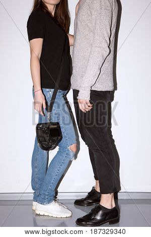 Unrecognizable casual couple with camera near white wall. Female photographer and male model posing for photo. Friendship of sexes, professional unity, communication at work concept