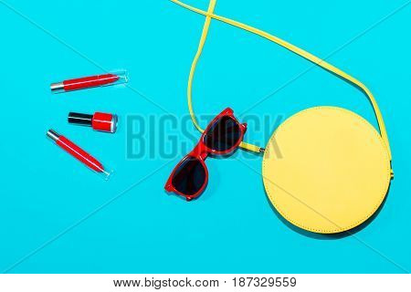 Colorful stylish woman summer accessories collection on blue background, top view