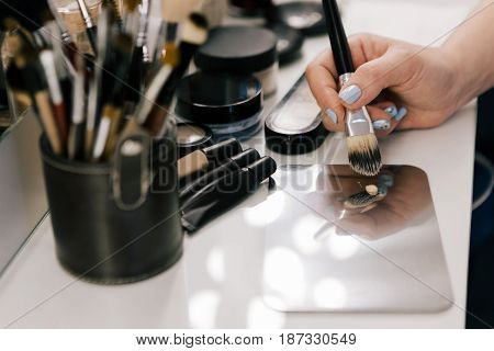 Hand of unrecognizable person holding a brush for makeup. The make-up artist prepares to apply a foundation. Professional workplace in salon.