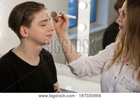 Horizontal indoors shot of beautician woman applying makeup on man sitting with eyes closed. Male beauty , gender equality concept.