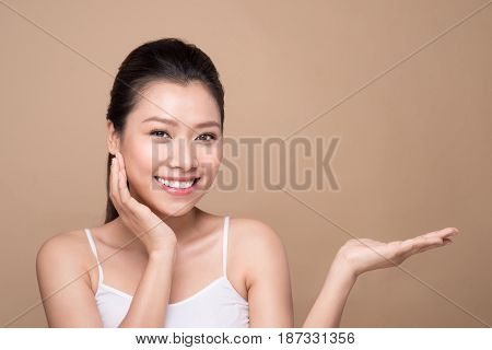 Proposing A Product. Beautiful Spa Woman Showing Empty Copy Space On The Open Hand Palm