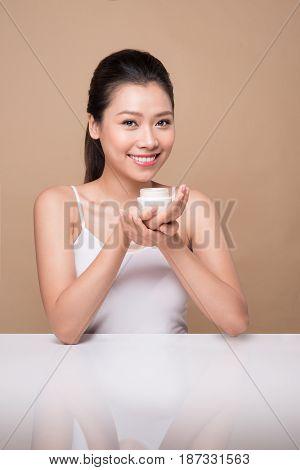 Skincare. Beautiful Asian Woman Show Moisturizer Or Lotion Product.