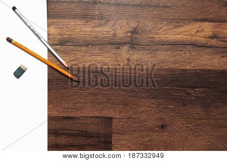 From above pencils and rubber lying on a sheet of paper on wooden background. Drawing lessons, art school, young artist concept