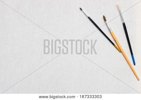 White canvas and painting brushes. Professional painter workplace flat lay. Artist's equipment assortment background. Drawing lessons, art school, young painter, creativity, DIY concept