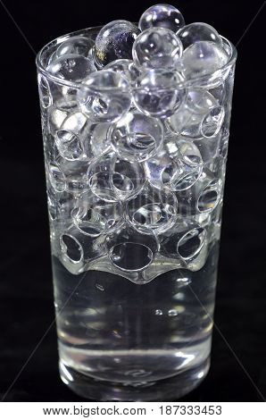Silicone balls in a glass with water on a black background