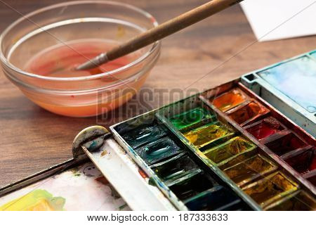 Watercolor artist workplace close up. Palette of paints, brush, dirty water. Drawing lessons, art school, young artist, creativity concept