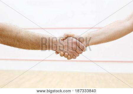 handshaking before match in squash. Two men are going to have sport battle. Photo with selective focus. Squash players shaking hand before match in court