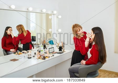 professional makeup artist doing makeup for young woman. Make-up artist at work in beauty salon. Backstage photo as visagiste applying makeup