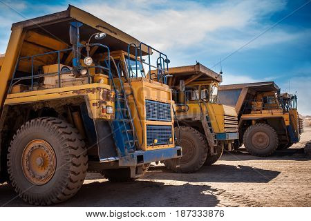 Yellow dump trucks ready to work in a mining