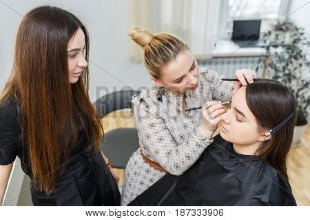 Makeup course at beauty school. Professional makeup artist conducts a master class. Make-up artist applying makeup