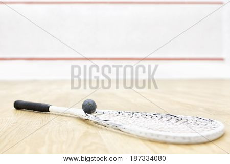 one squash racket and ball on the wooden floor. Racquetball equipment on the court and wall with red lines on the background. Photo with selective focus