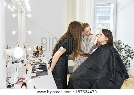 professional makeup artist conducts a master class. Make-up artist work in her studio. Visagiste applying makeup