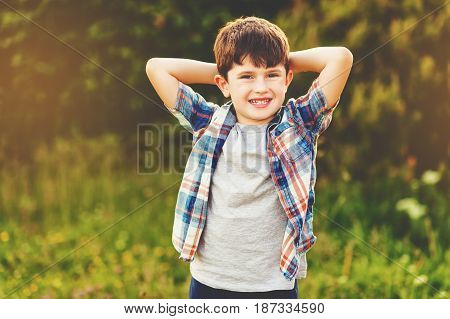 Happy kid boy of 6 year old having fun outdoors wearing blue plaid shirt