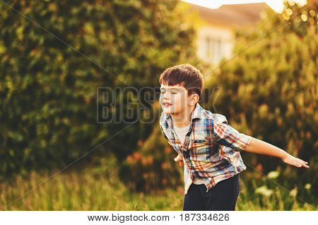 Happy kid boy of 6 year old having fun outdoors wearing blue plaid shirt, pretending to be a plane, eyes closed