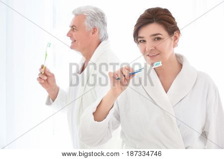 Senior woman and her husband cleaning teeth at home