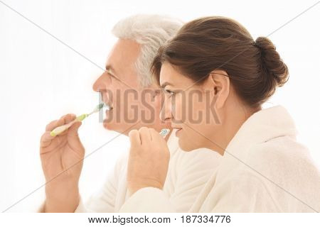 Senior couple cleaning teeth at home