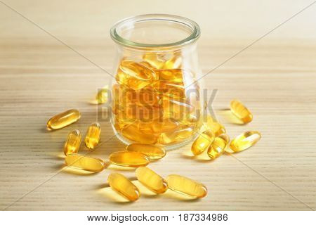 Glass bottle with fish oil capsules on light wooden background