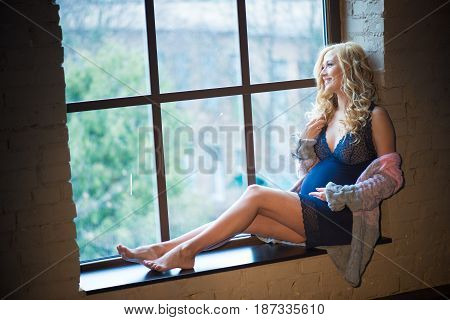 Beautiful red-haired pregnant girl sitting on the window