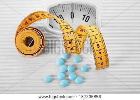 Diet concept. Measuring tape with pills and scales on background