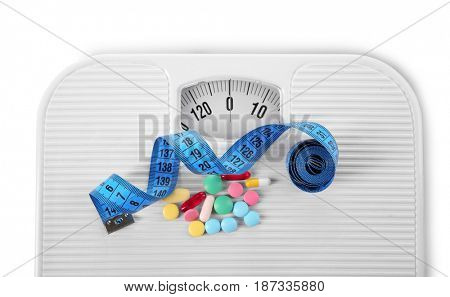 Diet concept. Measuring tape, assorted pills and scales on white background