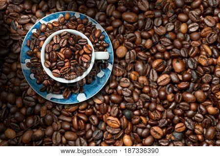 Coffee cup with roasted coffee beans on a background with many coffee beans