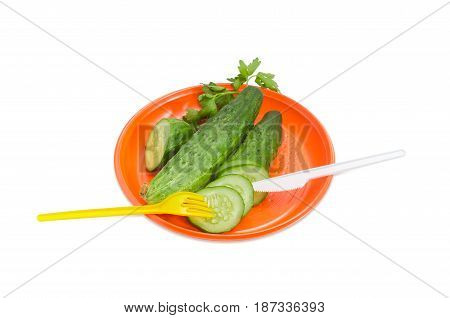 Orange disposable plastic plate whole and sliced cucumbers with disposable plastic fork and knife on it on a light background