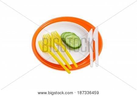 Orange and white disposable plastic plates different sizes and several slices of the cucumber on them plastic disposable yellow forks and white knives on a light background
