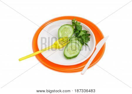 Orange and white disposable plastic plates different sizes and several slices of the cucumber twig of the parsley plastic disposable fork and knife on them on a light background