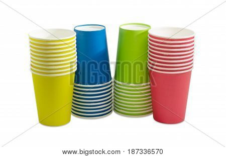 Four piles of the disposable paper cups in red green blue and yellow colors on a light background
