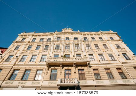 Riga, Latvia. Bottom View Of Main Facade Of Old Building In Classical Style, Decorated By Pilasters, Pediment And Balcony On Jekaba Street In Old Town In Sunny Day Under Blue Clear Sky.