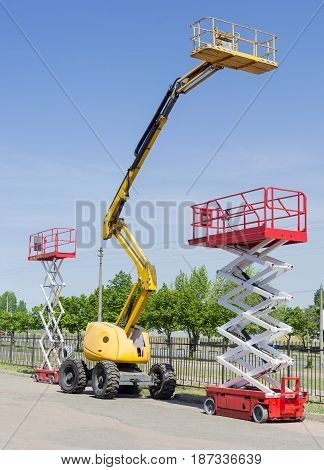 Two scissor wheeled lifts and one wheeled articulated lift with telescoping boom and basket on an asphalt ground