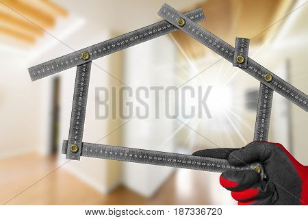 Interior Design Concept - Hand with work glove holding a metal meter ruler in the shape of house. Interior of a blurred house
