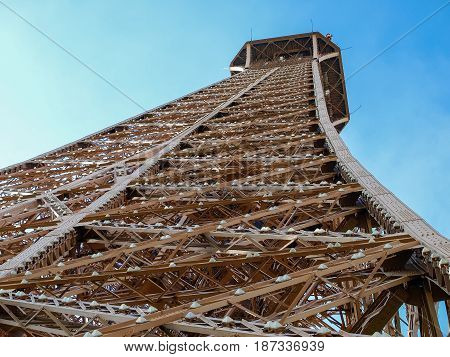Bottom view closeup of the fragment of the top part of the Eiffel Tower in Paris