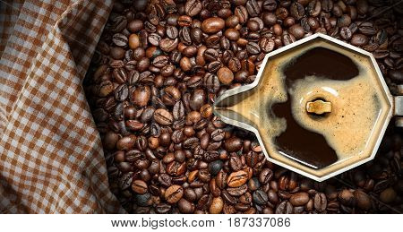 Old italian coffee maker (moka pot - top view) with roasted coffee beans on the background with a checkered tablecloth