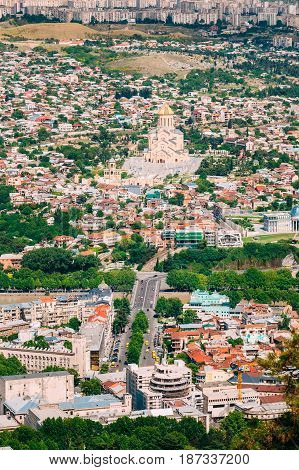 Tbilisi, Georgia. Aerial View Of Baratashvili Bridge Over Kura River And Sameba Complex, Holy Trinity Cathedral, Surrounded By Private Residential District In Sunny Summer Day.
