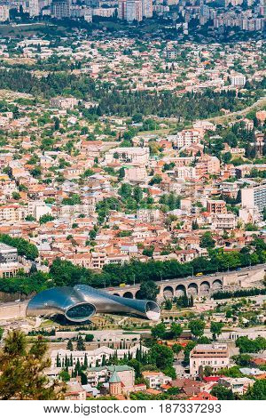 Tbilisi, Georgia. Aerial View Of Music Theatre, New Cultural Center With Rike Park And Stone Baratashvili Rise. Residential Districts Background In Sunny Summer.