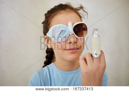 Closeup face of girl in dark sunglasses with one lens wrapped by piece of fabric and finger in removable plaster cast.