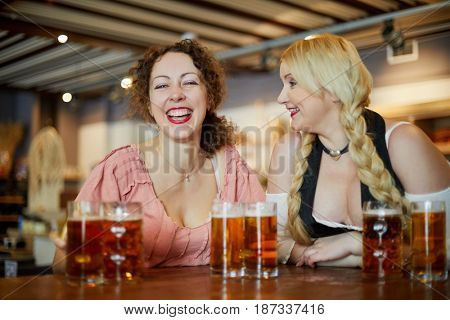 Two laughing women at bar counter with glass mugs with beer.