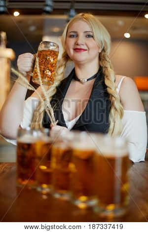 Smiling blonde woman stands holding spikelets in one hand and mug of beer in another at bar counter in cafe, focus on mug.