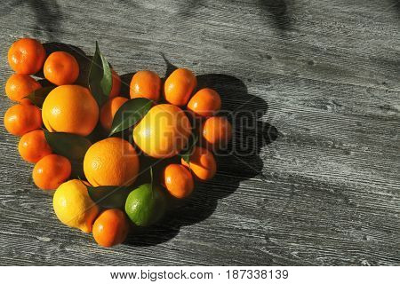 Appetizing fresh citrus fruits in shape of heart on wooden background