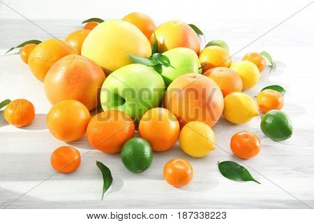 Appetizing fresh citrus fruits and apples on white wooden background