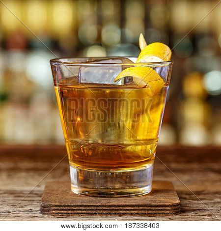 A strong alcoholic cocktail in a glass of old fashion is on the bar in the restaurant. Space for text