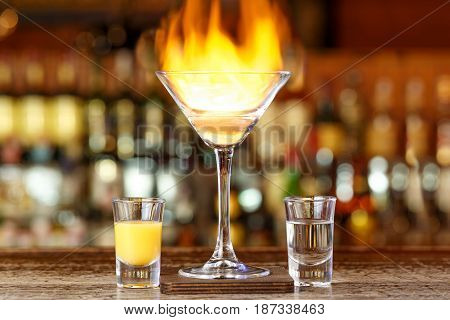 Club cocktail with fire in a bar on a blurry background of alcohol. Cocktail party unusual cocktails